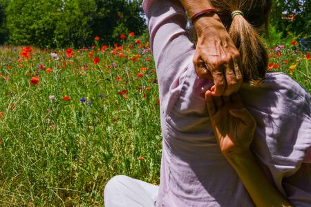 Woman sitting with arms in the back during a moment of meditation in the middle of nature