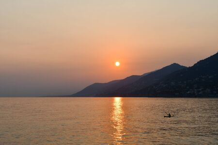A kayak alone when the sun goes down and the view on the headlands of northern Italy turns red