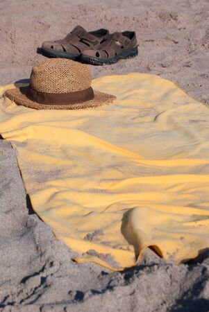 Leather sandals and wicker hat resting on the yellow beach towel on the sandy beach during a sunny day