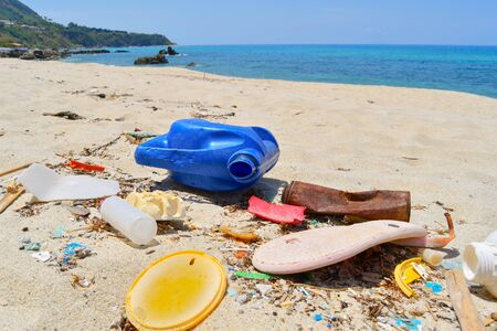 Plastic bottles cans and pieces of  different sizes abandoned on the beach Environmental disaster Imagens