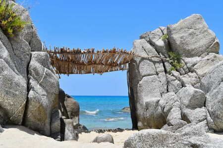 Bamboo reed-roofed hut resting on two large rocks and overlooking the sea