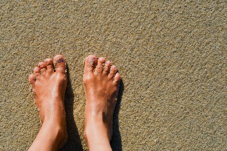 Two bare feet side by side on the wet sand 스톡 콘텐츠
