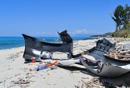 Plastic bottles and piece of a car abandoned on the beach Environmental disaster 스톡 콘텐츠