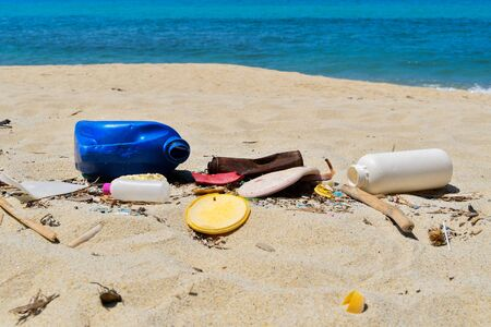 Plastic bottles and cans of different sizes abandoned on the beach Environmental disaster