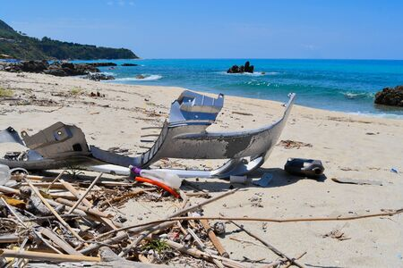 Bumper of a car and other trash on a beach near the turquoise sea