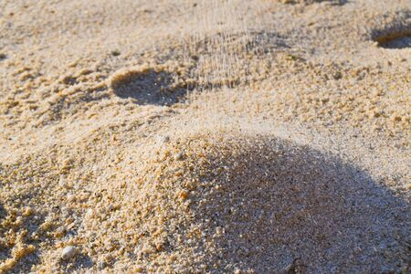 Sand with warm colors dropped gradually over a small freshly formed mountain