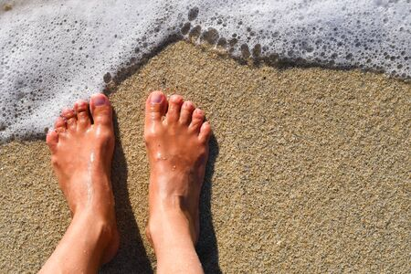 Two bare feet side by side on the wet sand with a bit of foam of the sea