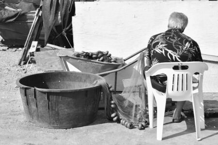 Black and white of a fisherman sitting with the nets next to him