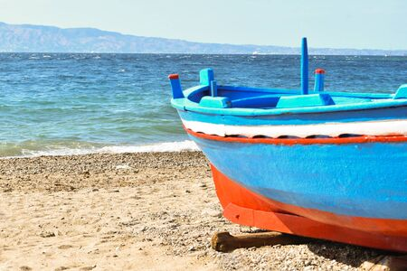 Characteristic colored fishing boat on the beach with rough sea