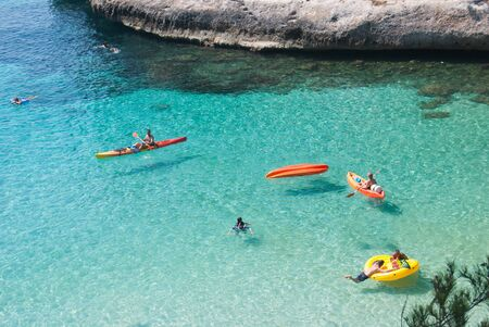 Three kayaks and swimmers in a heavenly turquoise sea
