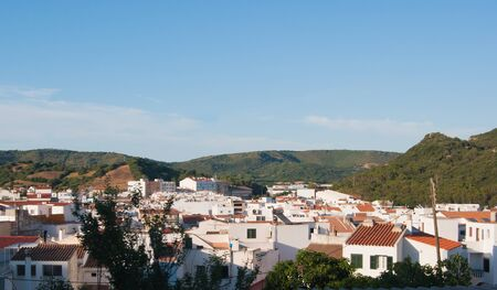 White houses of the Ferreries village with green hills around in Menorca one of the Spanish island