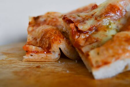 Two pieces of margherita pizza over a wooden table and on a white background
