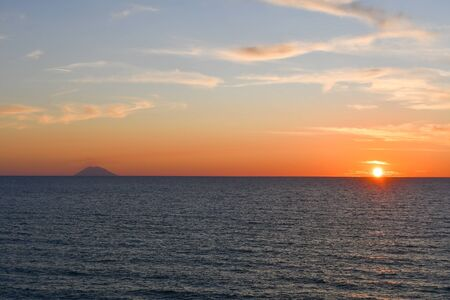 Orange sun just above the horizon line of the sea in southern Italy