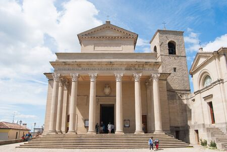 Facade of the main church with columns and a few tourists Stock Photo