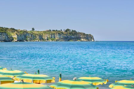 Panoramic views of the coast from above the green and yellow umbrellas of Tropea beach in Calabria