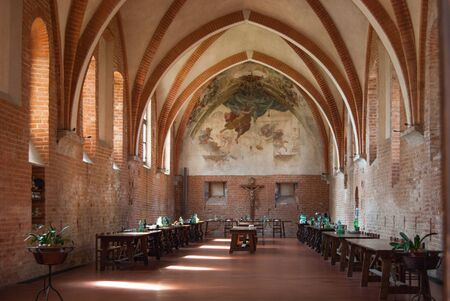 Ancient canteen with frescoes on the walls and tables ready inside the Cistercian abbey of Milan in northern Italy