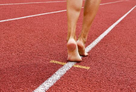 Feet of woman on a white line of the track athletics - concept of marketing business and sales increase Stock Photo