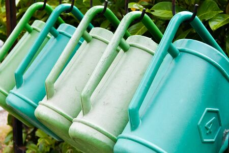 Five watering cans side by side hanging from the cemetery