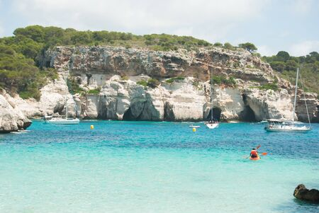 Panoramic view of the pink rock coast and the turquoise sea sailing boats of the Spanish island 스톡 콘텐츠