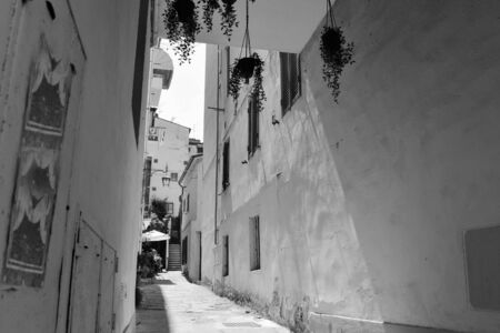 Particular shadows in a narrow street in Italy Black and white 스톡 콘텐츠
