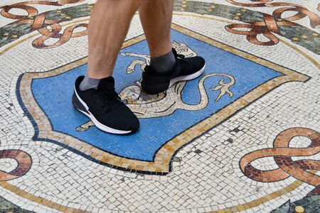 Tourist doing three laps with the heel on the balls of bull on the floor as brings luck - Legend about bringing luck in the north of Italy Stock Photo