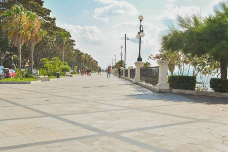 Large tiled promenade along the sea with palm trees in the city in southern Italy
