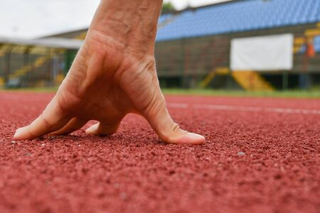 Blurred hands to the side with the finish point on the horizon of an athletics track in focus 스톡 콘텐츠