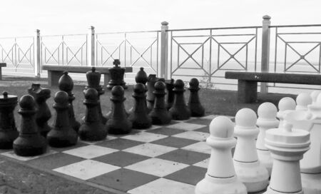 Black and white chess set on a large chessboard on a terrace on the sea before the game starts 스톡 콘텐츠