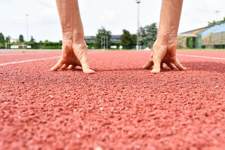 Hands of girl in position for start on the red carpet of athletics