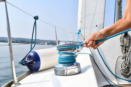 Hand with blue nail polish of a young woman working on a sailboat 스톡 콘텐츠