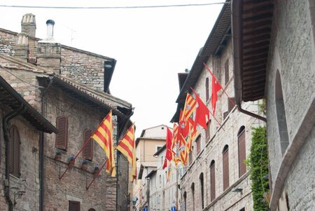 Flags from several wards hang on the walls of houses in the city of Assisi in Tuscany