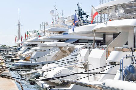 Large luxury white boats side by side tied to the harbour with flags from different nations