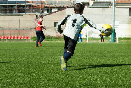 Young football player with number one on his uniform during a game on green grass 스톡 콘텐츠