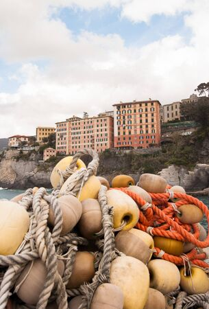 Pile of networks offisherman with characteristic coloreted houses of Liguria as background 스톡 콘텐츠