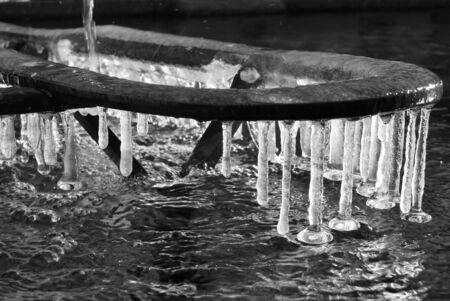 Iced water with icicles attached to a metal structure of a fountain