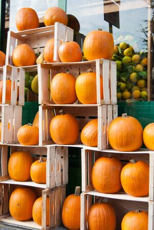 Creative exposition of wooden boxes with many orange pumpkins outside of a greengrocer