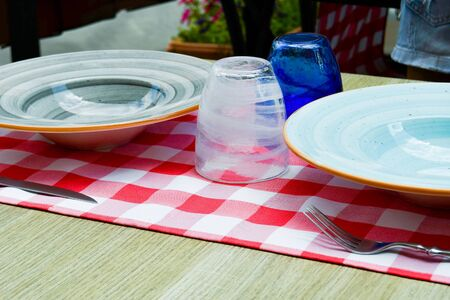 White and blue glasses and ceramic plate on the table in the open air