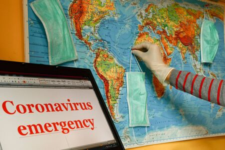 Hand with latex glove while hanging a medical mask on the world map and words Emergency Coronavirus on a laptop
