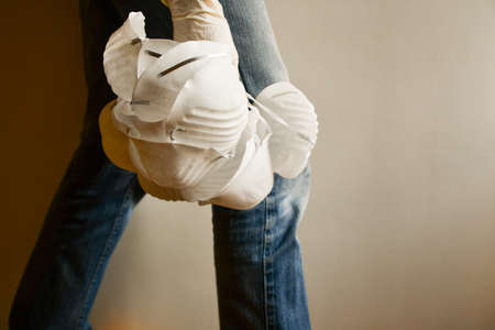 Girl in jeans with many white surgical masks hanging in hand with disposable latex glove