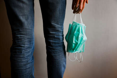 Girl in jeans with three surgical masks hanging in her hand 스톡 콘텐츠