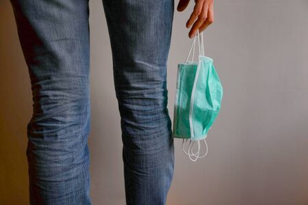 Girl in jeans with three surgical masks hanging in her right hand