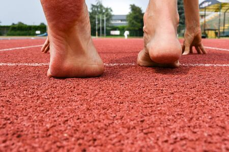 Feet of girl in position for start on the red carpet of athletics