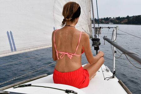 Woman with crossed legs in meditation position at the front and while the sailboat goes 스톡 콘텐츠