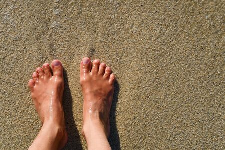 Two barefeet side by side on the clean wet brown sand