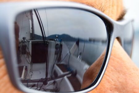 The dark glasses of a skipper with the len reflecting the cabin and the equipment of the boat