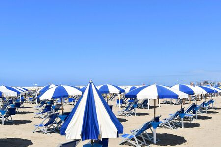 Open umbrellas and well lined blue and white sbraes chairs on the sandy beach without people