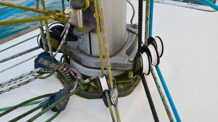Coils and ropes at the base of the main mast of the sailboat