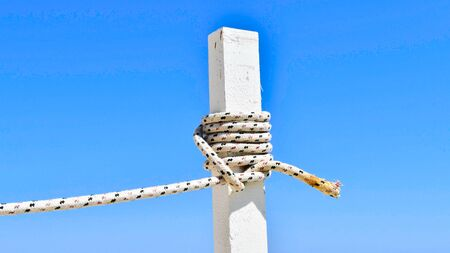 White wooden stake with colored rope wrapped around in contrast to the clear blue sky Banco de Imagens