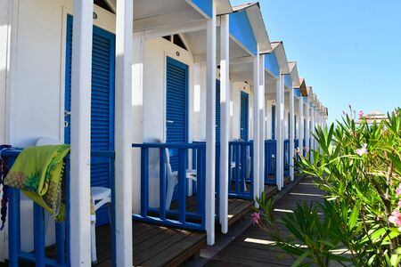 Row of empty blue changing rooms on the beach of a balearic lido and flowering plant