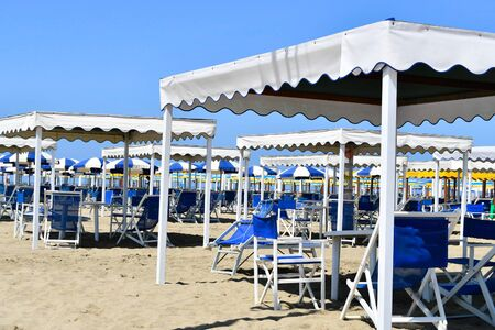 Group of well-aligned white gazebos and beach chairs on the sandy beach without people Banco de Imagens